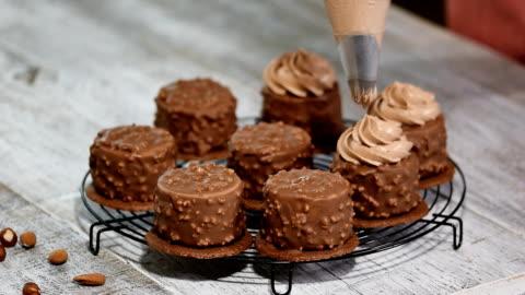 vídeos y material grabado en eventos de stock de decoración de pastel de chocolate mousse mini. torta de mousse de chocolate avellanas cubierto con glaseado de chocolate. - postre