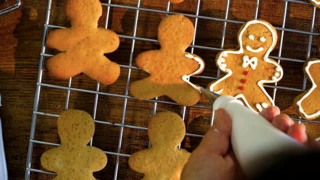 Decorating Christmas Cookies with Icing Decorating gingerbread man Christmas Cookies with colorful icing gingerbread man stock videos & royalty-free footage