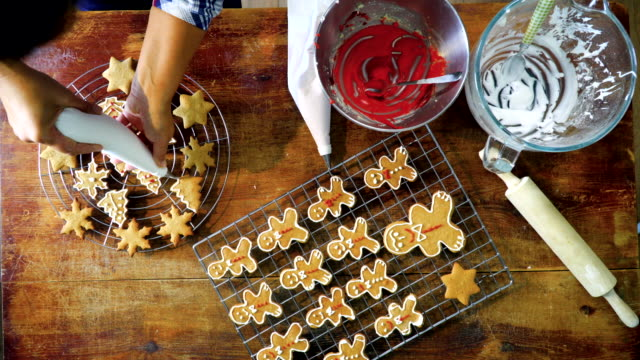 vídeos de stock e filmes b-roll de decorating christmas cookies with icing - assado no forno
