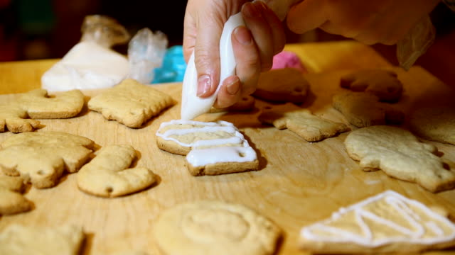 vídeos de stock e filmes b-roll de decorating christmas stocking cakes by hand with icing sugar. - christmas cake