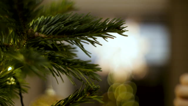 Decorating Christmas tree close-up of a woman hands hanging Christmas ornaments in the tree. christmas ornament stock videos & royalty-free footage