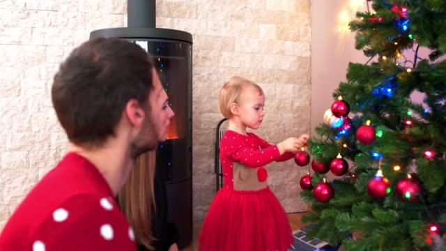 vídeos de stock e filmes b-roll de decorating christmas tree - enfeitado