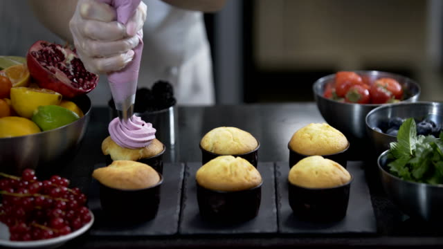 Decorating cup cake with cream. Using cooking bag, confectioner making muffins