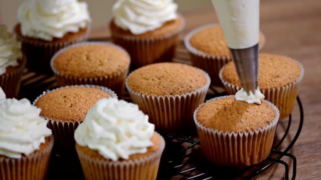 クリーム カップ ケーキを飾る。おいしいケーキにバター クリームを入れて女性の手のショット - カップケーキ点の映像素材/bロール