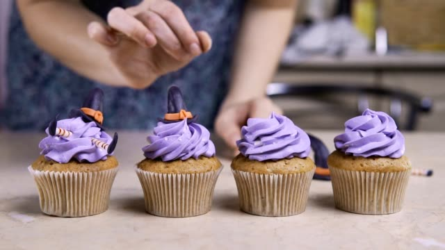 vídeos de stock e filmes b-roll de decorating cupcake with icing hat and legs. muffin like witch. halloween concept - bolo de bolacha
