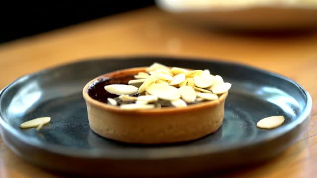 vídeos de stock e filmes b-roll de slomo decorating dark chocolate pie with sliced almond - bolo sobremesa