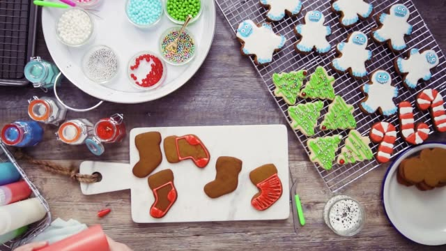 vídeos de stock e filmes b-roll de decorating gingerbread and sugar cookies - christmas cookies