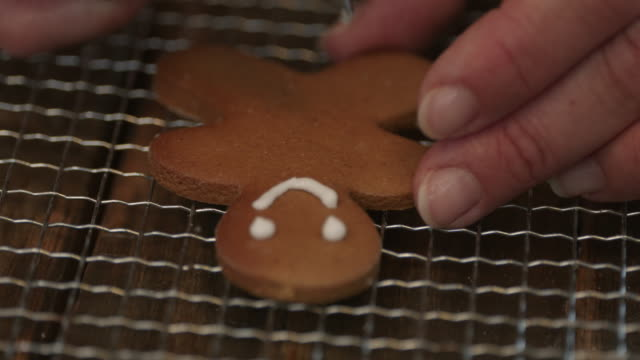 Decorating Gingerbread Cookies with Icing Decorating Gingerbread Cookies with Icing - 4k video gingerbread man stock videos & royalty-free footage