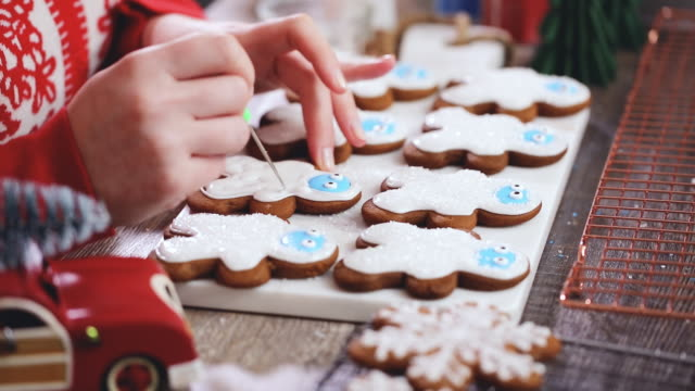vídeos de stock e filmes b-roll de decorating gingerbread cookies with royal icing. - christmas cookies
