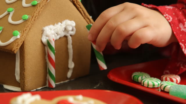 decorating gingerbread house for christmas - decorare video stock e b–roll