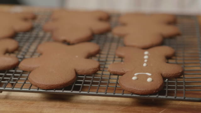 vídeos de stock e filmes b-roll de decorating gingerman bread - christmas cookies