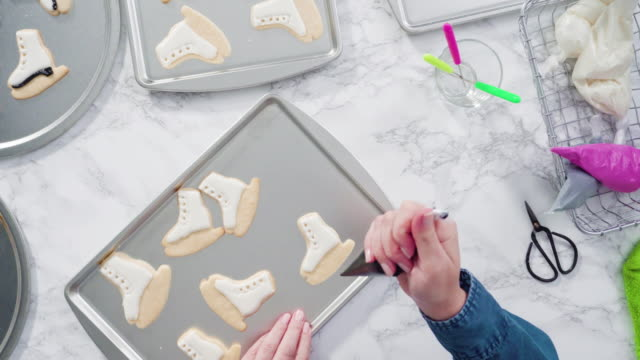 decorating ice skate shaped sugar cookies with black color royal icing. - articoli casalinghi video stock e b–roll
