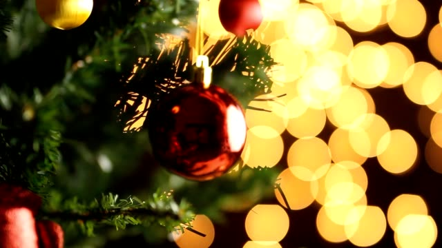 Decorating red ball on christmas tree