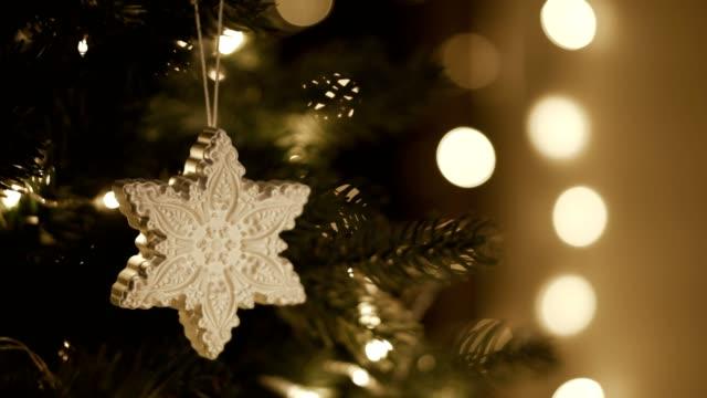 decorando l'albero di natale, le decorazioni sono corrette. luci calde sullo sfondo - decorare video stock e b–roll