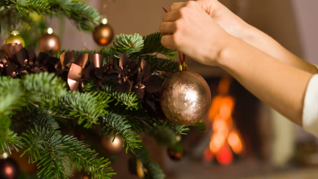 Decorating the christmas tree Woman decorating the christmas tree, hanging ornaments with fireplace burning in the background hanging stock videos & royalty-free footage
