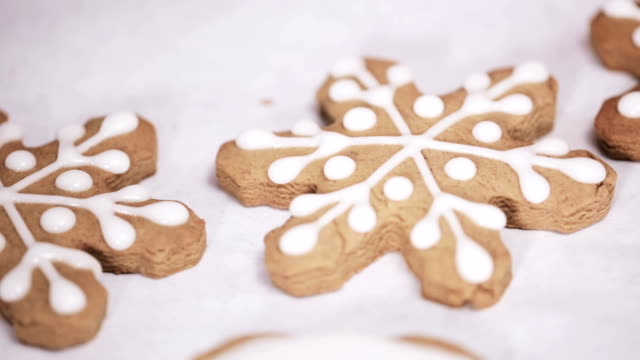 vídeos de stock e filmes b-roll de decorating traditional gingerbread cookies with royal icing for christmas. - christmas cookies