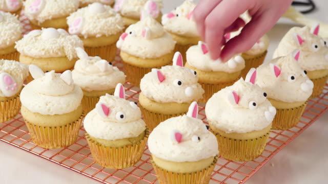 イースターのための白い buttercream のフロスティングでバニラカップケーキを飾ります。 - カップケーキ点の映像素材/bロール