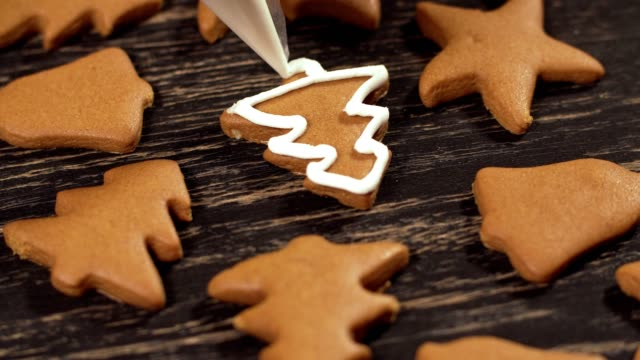 Decoration of Christmas cookies. Close up garnishing gingerbread Christmas tree Close up garnishing homemade gingerbread Christmas tree. Decoration process of Christmas cookies. Family culinary and traditions concept ginger spice stock videos & royalty-free footage