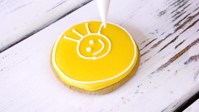 decorazione di biscotto con immagine solare sorridente. - arti e mestieri video stock e b–roll