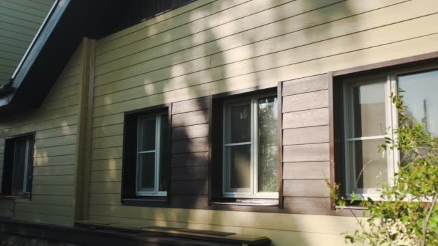 サイディングと家の装飾。ストック映像。家のファサードの木製の面。木製の質感の下で作られた家の美しいファサードの装飾 ビデオ