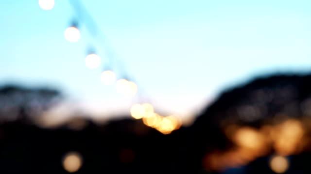 vídeos de stock e filmes b-roll de decoration outdoors string lights on soft blue sky in the evening, defocused with bokeh lights. - céu claro