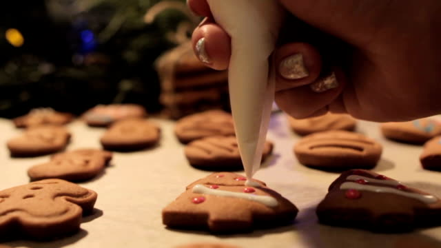 Decoration process of Christmas cookies Decoration process of Christmas cookies in motion. Close up woman garnishing with white icing homemade gingerbread scones on festive illuminate background. Family culinary and traditions concept cookie stock videos & royalty-free footage
