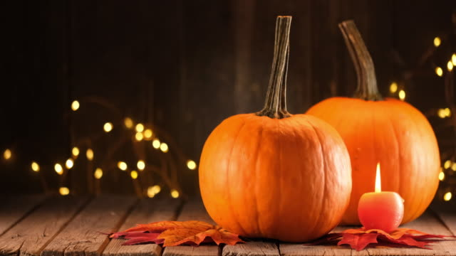 Decoration with pumpkins on illuminated background and a rustic wooden table