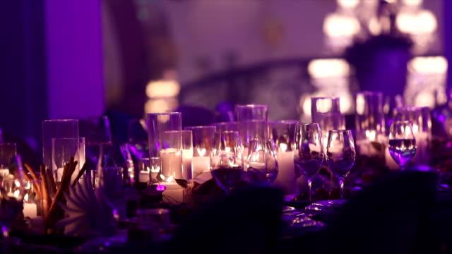 vídeos de stock e filmes b-roll de decorative candles on the dining table, glasses and christmas candles on the table, white wax candleswith glass candlestick, candle with glass candlestick, restaurant, interior, close-up - muita comida