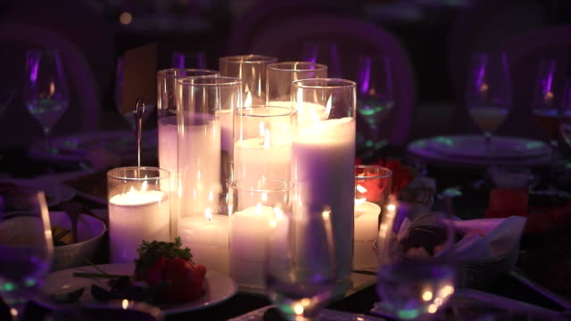 Decorative candles on the dining table, glasses and Christmas candles on the table, white wax candleswith glass candlestick, Candle with Glass Candlestick, restaurant, interior, close-up video