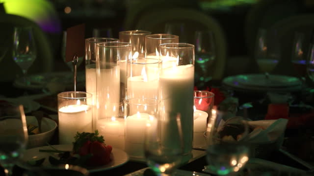 Decorative candles on the dining table, glasses and Christmas candles on the table, white wax candleswith glass candlestick video