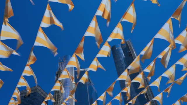 decorative flags flying on the wind against a blue sky, with skyscrapers in the backdrop. high line park, manhattan, new york city, usa - memorial day weekend stock videos & royalty-free footage