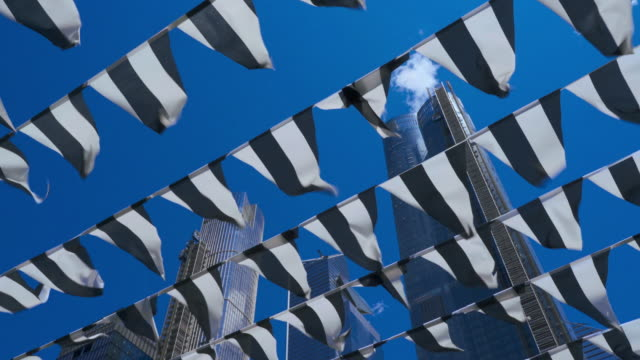 Decorative flags flying on the wind against a blue sky, with skyscrapers in the backdrop. High Line Park, Manhattan, New York City, USA
