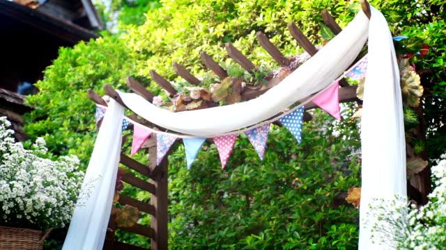 Jardín decorativo para ceremonia de boda, decorada con tela blanca y flores frescas. - vídeo