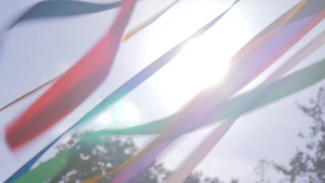vídeos de stock, filmes e b-roll de fitas multicolor decorativas que acenam no vento - insígnia