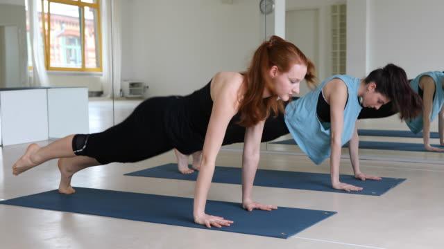 Dedicated women exercising yoga at health club video