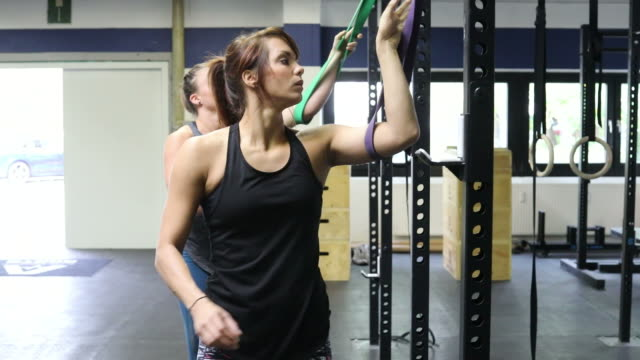 Dedicated women pulling resistance bands in gym video