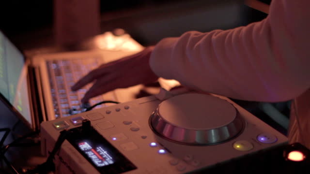Deejay's hands playing set at party, nightclub atmosphere video