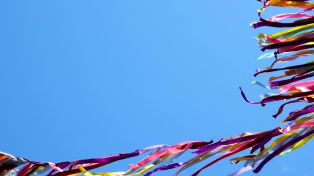 djupblå himmel och band med olika färger viftande i vinden. - blue yellow band bildbanksvideor och videomaterial från bakom kulisserna