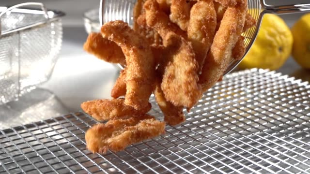 Deep Fried Chicken Strips A freshly cooked basket of breaded chicken strips being poured onto a rack. finger stock videos & royalty-free footage