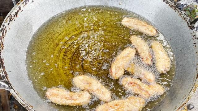 タイの屋台の食べ物で伝統的な鍋にバナナを揚げます。 - 油料理点の映像素材/bロール