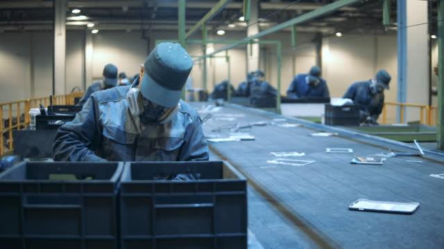 l'elettronica difettosa viene smistata dai lavoratori delle discariche. i dipendenti delle fabbriche maschili stanno smistando i rifiuti. - industria elettronica video stock e b–roll