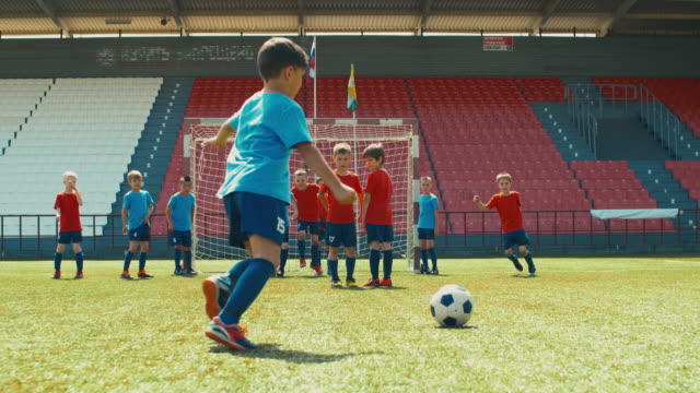 Defensive ball in youth soccer match Small boy in professional soccer uniform kicking ball through defensive wall on training goal post stock videos & royalty-free footage