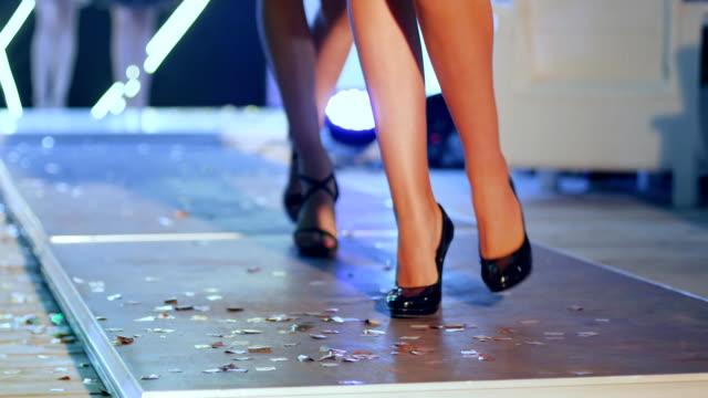 Desfiladero de mujer en calzado cómodo ir a lo largo de la pasarela en la semana de la moda - vídeo