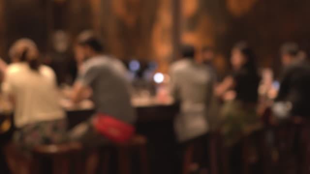 ludzie defocus siedzą w barze i piją w ciemnym barze - bar filmów i materiałów b-roll