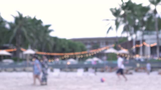 Defocus people walk on beach and play ball