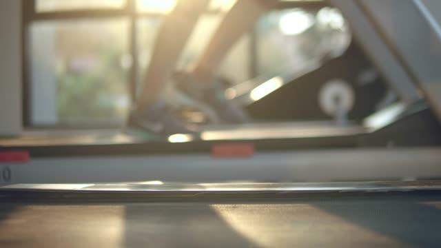 디 포커스: 젊은 여자 운동 및 체육관에서 디딜 방 아에 조깅 - 체육관 스톡 비디오 및 b-롤 화면