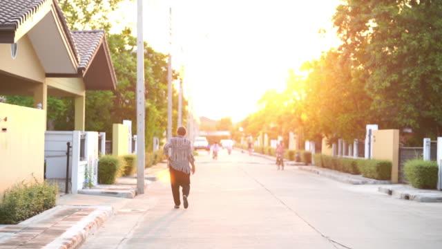 defokuserad bakgrund, asiatisk senior kvinna promenader, avslappningsövning - walking home sunset street bildbanksvideor och videomaterial från bakom kulisserna