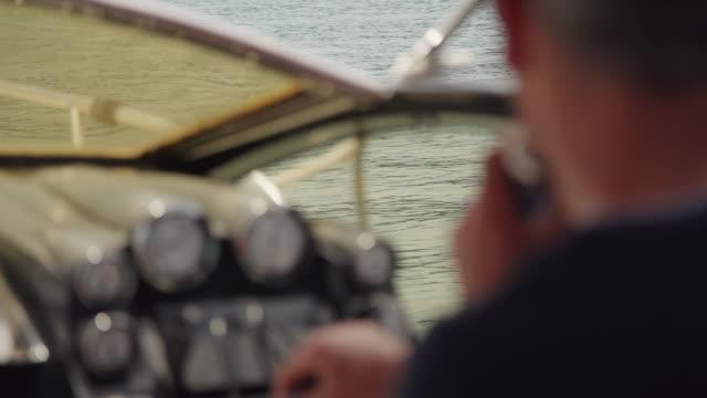 defocused blurred abstract old man driving yacht, turning steering wheel - ster fragment pojazdu filmów i materiałów b-roll