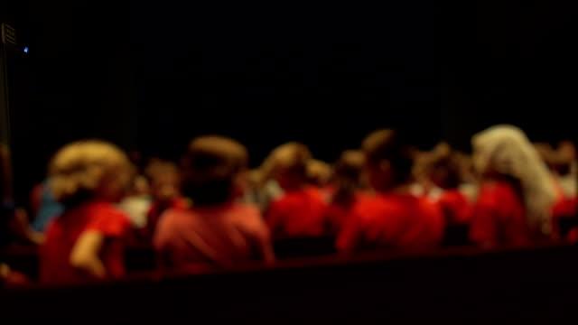 Defocused child audience in theater premiere video