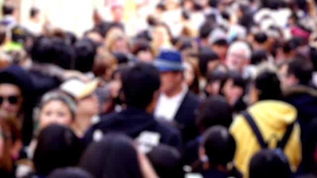 sfocato folla di persone a piedi in una trafficata strada di tokyo - city walking background video stock e b–roll